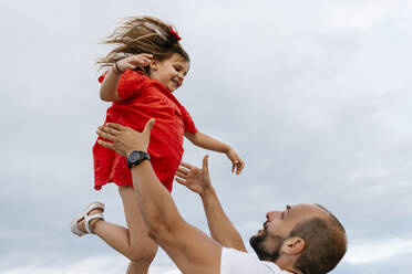 Happy father lifting daughter against sky - EGAF00374