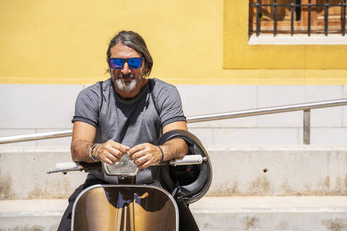 Mature man wearing sunglasses while sitting on motor scooter during sunny day - DLTSF00815