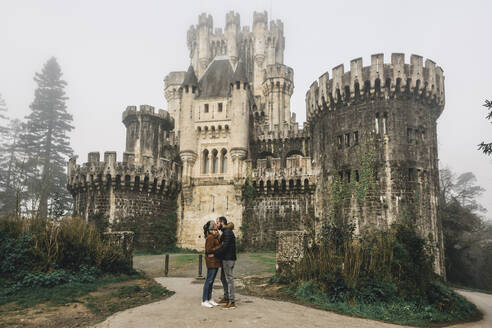 Couple kissing while standing against Butron Castle, Basque Country, Spain - XLGF00295