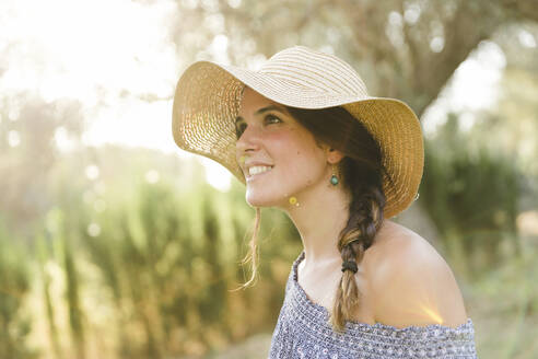 Thoughtful young woman wearing sun hat during sunny day - LVVF00145