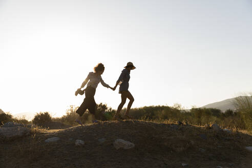 Female friends holding hands while walking on hill at countryside - LVVF00151