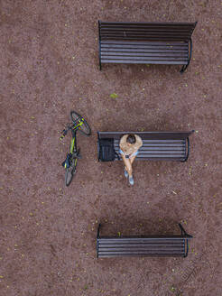 Aerial view of woman using smart phone while sitting on bench in park - KNTF04805