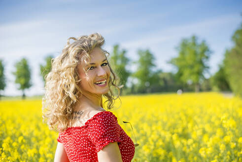 Smiling mature woman wearing red dress standing against oilseed rapes - BFRF02255