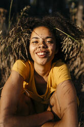 Close-up of smiling young woman with afro hair sitting in forest - TCEF00869