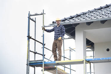Construction worker standing on scaffold against clear sky at construction site - MJFKF00394