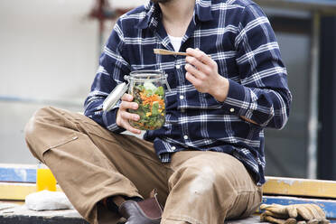 Close-up of construction worker holding salad in jar while sitting outdoors at site - MJFKF00406