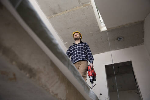 Construction worker holding power tool while walking in renovating house - MJFKF00412