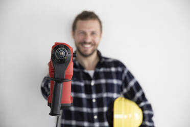 Construction worker holding work tool and helmet while standing against wall in house - MJFKF00415