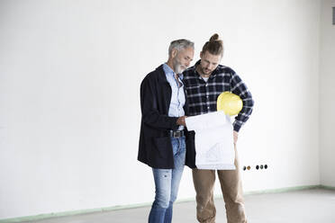 Architect and construction worker discussing blueprint while standing in empty house - MJFKF00418