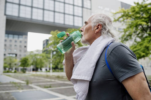 Close-up of senior man drinking water while standing in city - MEUF01155