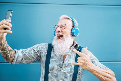 Man Listening Music On Smart Phone While Gesturing Against Wall - EYF09429