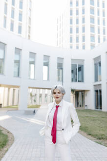 Young woman wearing white suit standing on footpath against buildings in city - TCEF00880