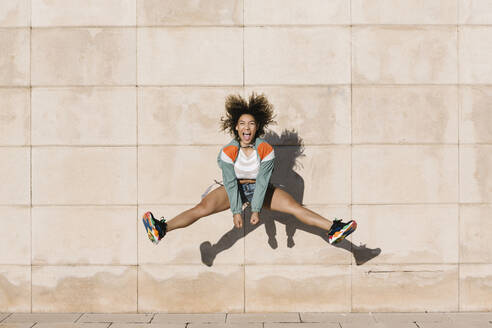 Excited young woman screaming while jumping against wall during sunny day - XLGF00308