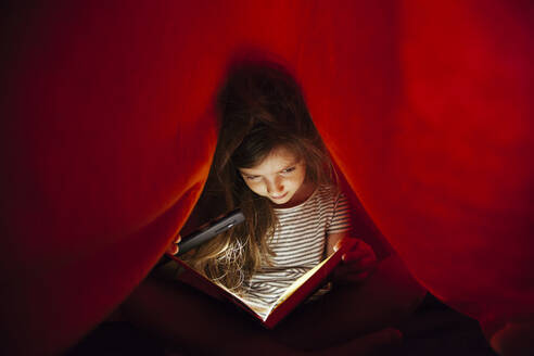 Close-Up Of Girl With Mobile Phone Light Reading Book Under Blanket - EYF09581