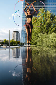 Sporty woman balancing plastic hoops on retaining wall in city - JMPF00114