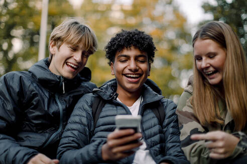 Happy teenage boy showing smart phone to male and female friends in city - MASF18515
