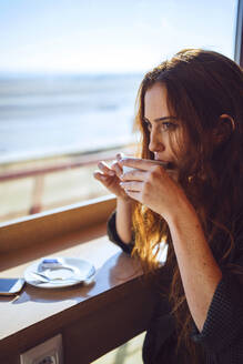 Thoughtful businesswoman drinking coffee at airport cafe - EHF00388