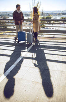 Business couple talking while standing on elevated walkway at airport during sunny day - EHF00403