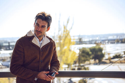 Thoughtful businessman holding smart phone while standing on elevated walkway during sunny day - EHF00415