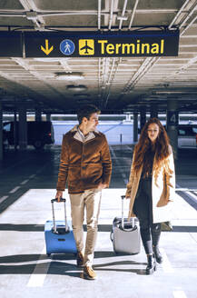 Business couple pulling luggage while walking under terminal sign at airport - EHF00433