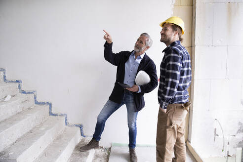 Male architect guiding construction worker while standing on steps in renovating house - MJFKF00421