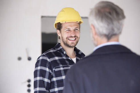 Smiling construction worker wearing hardhat talking with architect in constructing home - MJFKF00433