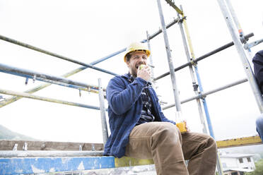 Construction worker eating food while sitting against clear sky at construction site - MJFKF00445