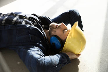 Close-up of construction worker with hands behind head sleeping on floor in renovating house - MJFKF00469