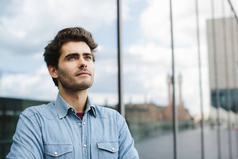 Close-up of thoughtful casual businessman looking away against modern building - SODF00823