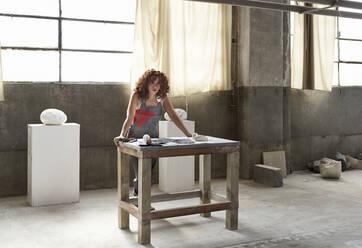 Female stonemason posing while standing by workbench in studio - VEGF02447