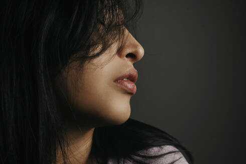 Close-up of woman with black hair against wall - DSIF00003