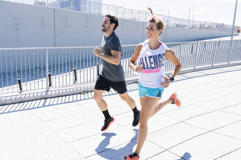Happy fit couple jogging on city street during sunny day - JCMF00936