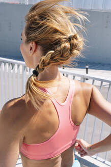Sporty woman with braided hair running during sunny day - JCMF00939