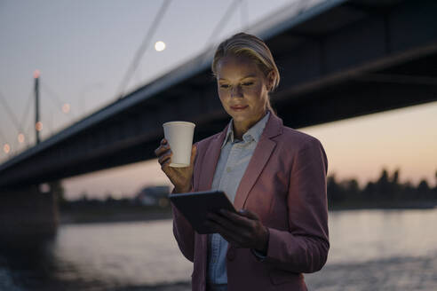 Beautiful businesswoman using digital tablet while holding disposable cup against bridge in city at dusk - JOSEF00993