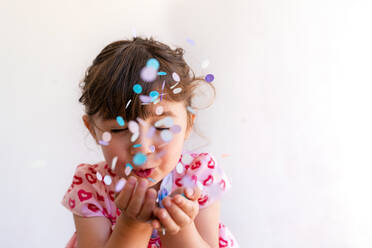 Close-up of cute girl blowing confetti from hands against white background - GEMF03923