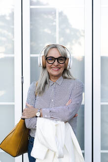 Smiling senior businesswoman with arms crossed listening music against office door - ERRF04104
