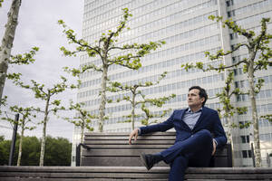 Mature businessman sitting on a bench in the city - JOSEF01151