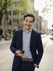 Portrait of a happy mature businessman with smartphone in the city - JOSEF01241