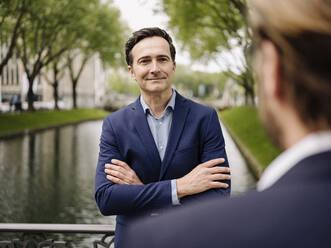 Portrait of a confident mature businessman with a colleague on a bridge - JOSEF01250