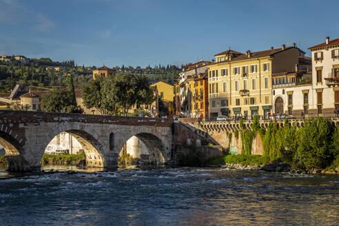 Italy, Veneto, Verona, Arch bridge over Adige river with city houses in background - NGF00560