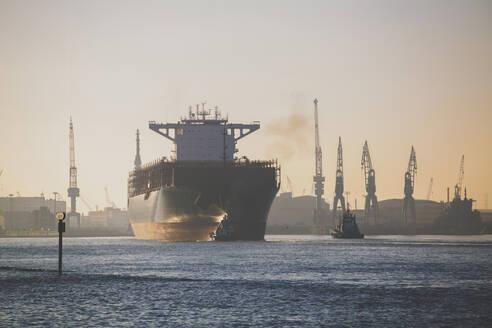 Germany, Hamburg, Ship leaving harbor at dusk - IHF00364