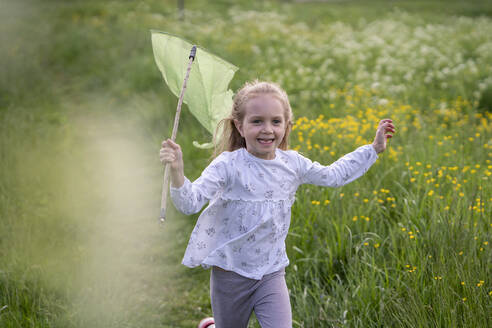 Smiling girl with butterfly net running on grassy land in forest - VPIF02546