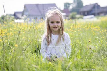 Smiling girl holding flowers sitting on grassy land - VPIF02549