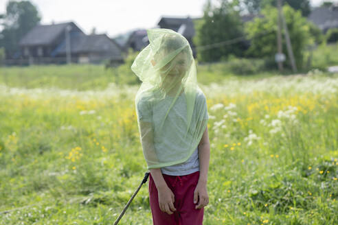 Playful boy wearing butterfly net while standing on grassy land - VPIF02552