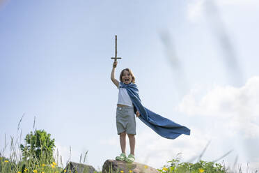 Boy wearing cape screaming while standing on rock against sky - VPIF02555