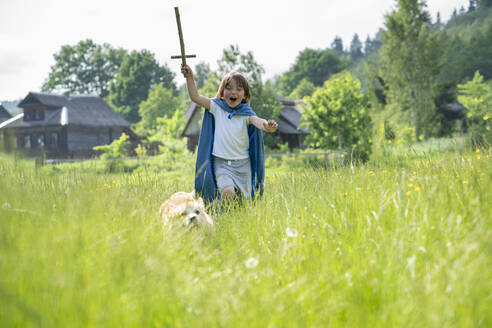 Playful boy wearing cape running with dog on grassy land - VPIF02558