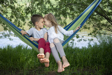 Cute friends with face to face sitting on hammock in forest - VPIF02564