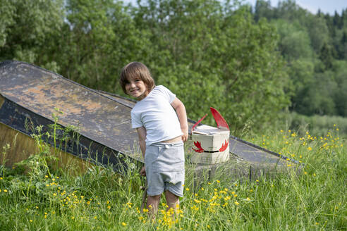 Smiling boy with mask on abandoned boat standing amidst plants in forest - VPIF02570