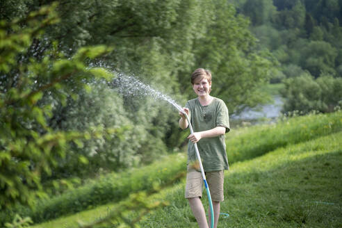 Smiling boy spraying water with hose in forest - VPIF02573