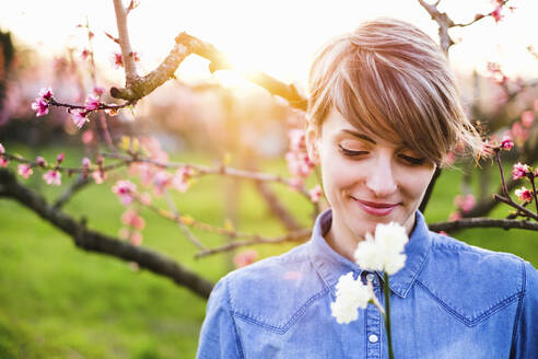 Close-up of smiling woman looking at flowers in park during sunset - SBAF00004
